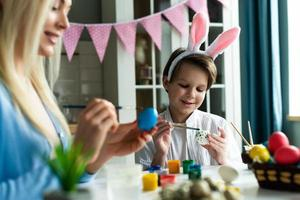 maman et fils décorent des œufs de pâques dans la cuisine. photo