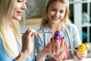 maman avec sa fille à colorier des œufs de pâques. photo