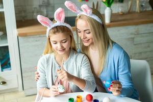 vacances de pâques, jour de pâques, famille heureuse, concept de vacances, mère et filles peignant des œufs de pâques. famille heureuse se préparant pour pâques. maman et ses filles jouent ensemble photo