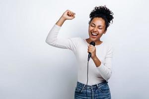 jolie fille chante dans un microphone, s'amuse à chanter sur fond blanc photo