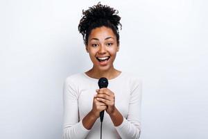 fille joyeuse avec un microphone dans ses mains sur un fond de mur blanc photo