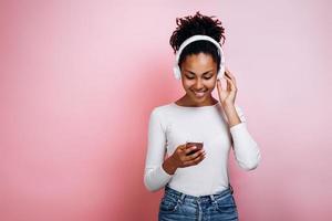jolie fille dans les écouteurs sur fond rose dans le studio allume la musique au téléphone photo