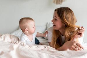 belle maman souriante et petite fille allongée sur le lit, s'amusant photo