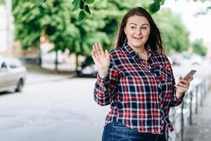 jolie fille dans la rue avec un téléphone dans les mains, souriant à quelqu'un et agitant la main photo