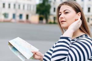 fille de voyage visitant la ville avec une carte dans ses mains et regardant autour. joyeuse touriste gaie explorant une nouvelle ville regardant sur le côté. photo