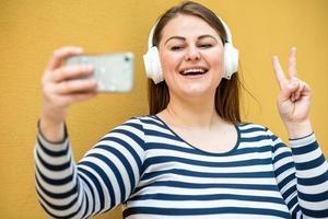 sur fond de mur orange, une femme souriante et joyeuse montre un geste de paix et prend un selfie sur un smartphone photo