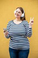 jolie femme souriante dans des écouteurs sans fil blancs montre un geste de paix sur fond orange photo