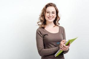 Jolie fille à lunettes prend des notes dans un cahier d'exercices sur fond blanc photo