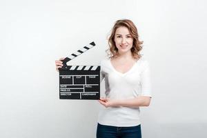 fille souriante tenant une planche de cinéma. photo