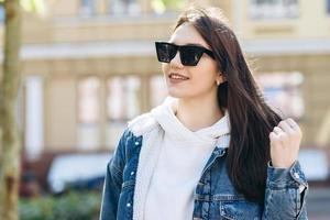 jolie fille aux cheveux noirs, vêtue d'un style décontracté, en lunettes de soleil, marchant dans la rue. photo