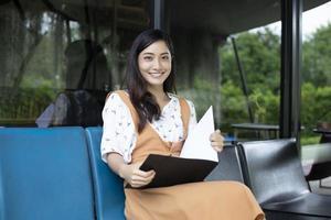 femmes asiatiques lisant et souriantes et heureuses de se détendre dans un café après avoir travaillé dans un bureau réussi. photo