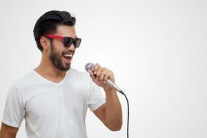 bel homme asiatique avec une moustache, souriant et chantant au microphone isolé sur fond blanc photo