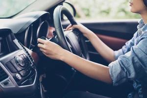 les mains de la femme asiatique bouton poussoir clignotant, bouton la voiture, mise au point sélective sur la main photo