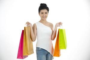 les femmes asiatiques et la belle fille tiennent des sacs à provisions et utilisent un téléphone intelligent et sourient tout en faisant des achats et en achetant avec une carte de crédit photo