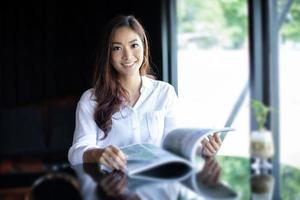 femmes asiatiques souriant et lisant un livre pour se détendre au café café photo