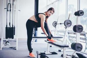 femmes asiatiques attachant des lacets de chaussures. les femmes de remise en forme se préparent à s'engager dans la salle de sport photo