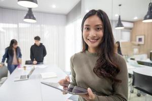 les étudiantes asiatiques sourient et s'amusent et en utilisant un téléphone intelligent et une tablette, cela aide également à partager des idées dans le travail et le projet. photo