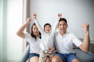 famille excitée et heureuse avec les bras levés en regardant la télévision à la maison photo