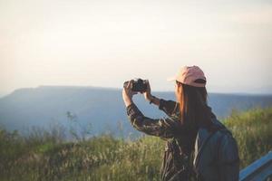 jeunes femmes asiatiques faisant de la randonnée avec des amis sacs à dos marchant ensemble et regardant la carte et prenant un appareil photo au bord de la route et ayant l'air heureux, détendez-vous pendant les vacances concept de voyage