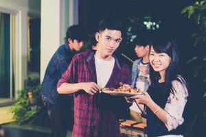 groupe d'amis asiatiques ayant un barbecue de jardin en plein air riant avec des boissons alcoolisées à la bière la nuit photo