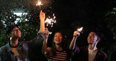 groupe d'amis asiatiques ayant un barbecue de jardin en plein air riant avec des boissons à la bière alcoolisées et montrant un groupe d'amis s'amusant avec des cierges magiques la nuit, mise au point douce photo