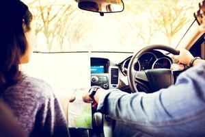 homme et femme asiatiques utilisant une carte lors d'un voyage sur la route et un jeune couple heureux avec une carte dans la voiture. mise au point floue et douce photo