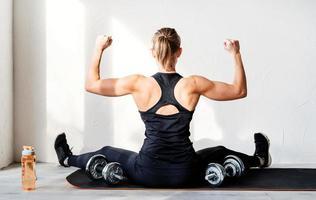 Vue arrière de la jeune femme blonde travaillant avec des haltères montrant ses muscles du dos et des bras photo