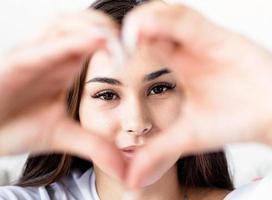Jeune femme brune heureuse en t-shirt blanc montrant le signe du coeur avec ses mains devant le visage photo