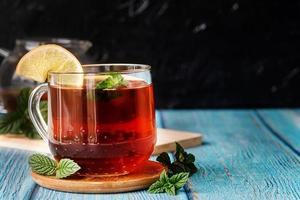 tasse de thé à la menthe et au citron isolé sur fond noir. photo