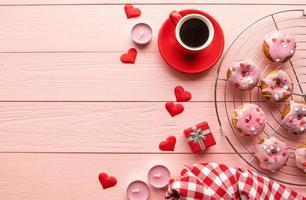 Valentin brackfast avec café et beignets isolé sur fond de bois rose photo