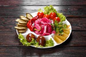 délicieux cornichons épicés coupés sur une assiette de service photo