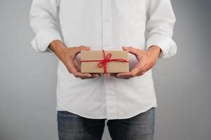 main tenant une boîte-cadeau, une boîte-cadeau de nouvel an, une boîte-cadeau de Noël, un espace de copie. noël, nouvelle année, concept d'anniversaire. photo