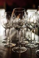 verres à vin vides. de beaux nouveaux verres à vin en verre se tiennent en rangées égales sur une table en bois dans un restaurant. mise au point sélective photo