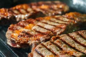 steak de faux-filet cru aux herbes et épices, friture sur une poêle à griller photo