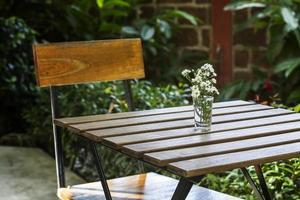 verre avec des fleurs sur une table en bois vintage photo