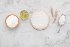 pâte à levure fraîche faite maison reposant sur fond de béton blanc à plat. photo