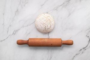 pâte à levure fraîche faite maison reposant sur une table en marbre avec des épis de blé et un rouleau à pâtisserie. photo