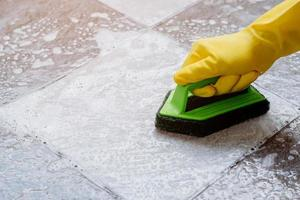 des mains humaines portant des gants en caoutchouc jaune utilisent un épurateur de sol en plastique de couleur verte pour frotter le sol carrelé avec un nettoyant pour sol. photo