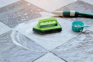 fermer la brosse en plastique verte pour frotter et nettoyer le sol est placée sur le sol carrelé humide et moussée avec un détergent. photo