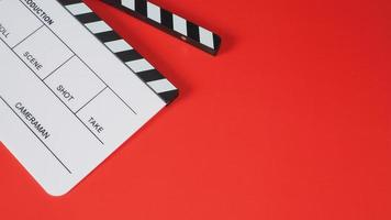 Clap ou ardoise de film sur fond rouge. Il est utilisé dans la production vidéo et l'industrie cinématographique. photo