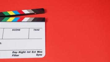panneau de clapet ou ardoise de film sur fond rouge. il est utilisé dans la production vidéo et l'industrie cinématographique. photo