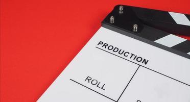 clap ou ardoise de cinéma. il utilise dans la production vidéo, le cinéma, l'industrie du cinéma sur fond rouge. photo