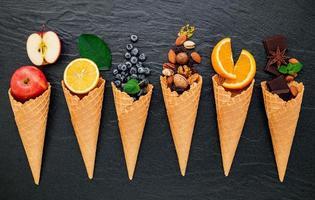 divers ingrédients pour la saveur de la crème glacée dans des cônes mis en place sur fond de pierre sombre. concept de menu d'été et sucré. photo