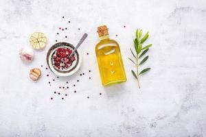 bouteille en verre d'huile d'olive et branche d'olivier sur fond de béton blanc. photo