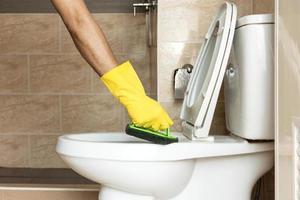 en utilisant une brosse en plastique pour frotter la cuvette des toilettes. photo
