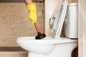 à l'aide d'un appareil pour réparer une cuvette de toilettes bouchée. photo