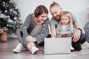 jeune famille de trois personnes utilisant un ordinateur portable en position allongée sur un tapis à la maison photo