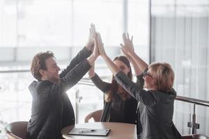 démarrer une entreprise. groupe de jeune architecte au bureau. groupe de partenaires commerciaux donnant cinq photo