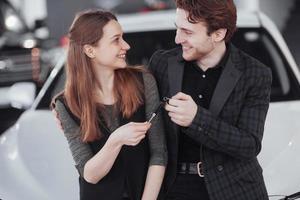 fiers propriétaires. beau jeune couple heureux étreignant debout près de leur voiture nouvellement achetée souriant joyeusement montrant les clés de voiture à la caméra copyspace famille amour relation style de vie achat consumérisme photo