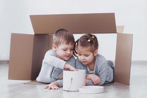 petit frère et petite soeur jouant dans des boîtes en carton en pépinière photo